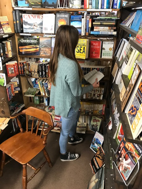 Woman reading books in a bookstore