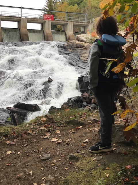 A young boy looking at water flowing from the High Falls Dam in Ontario.