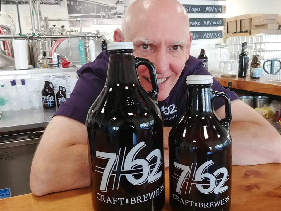 A man standing with two beer growlers from 7/62 Craft Brewers