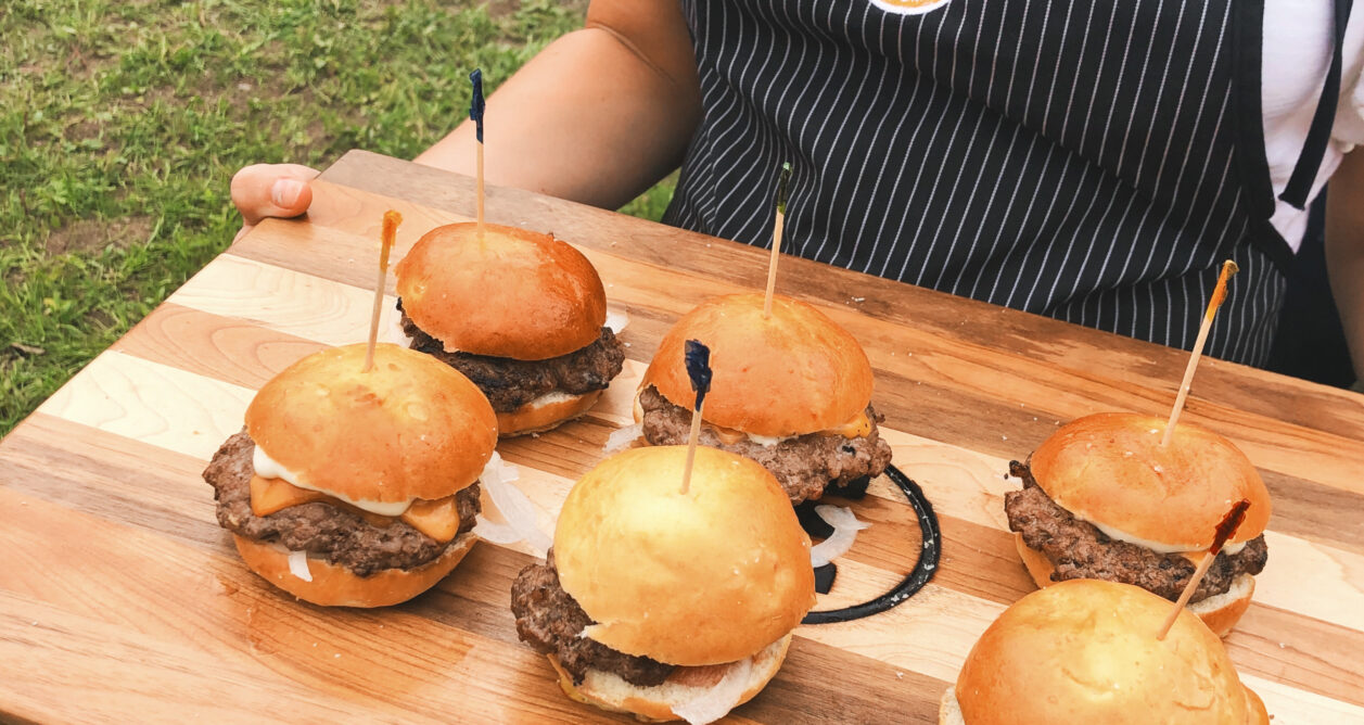 A half dozen hamb urgers on a cutting board held by a person