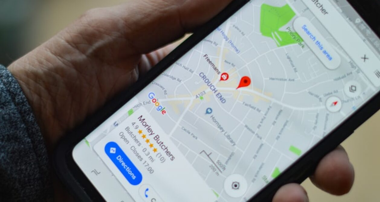 Hand holding mobile device that displays Google Maps app