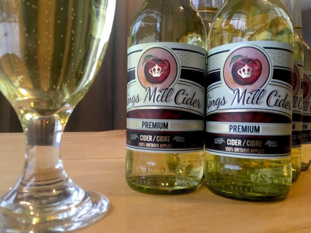 Glass bottles of apple cider from Kings Mill Cider on display with a wine glass filled with cider.