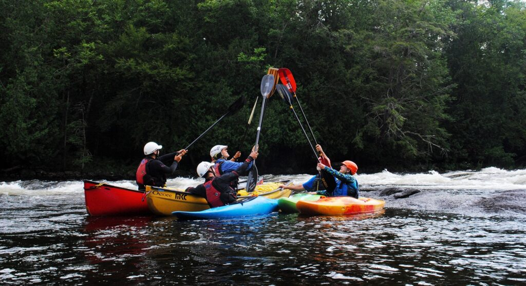 Five people in kayaks with their paddles in the air on a river.