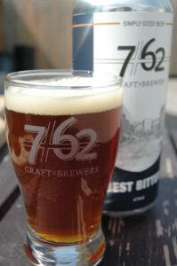 A glass of poured beer in the 7/62 Craft Brewers branded glass, beside a can of Best Bitter beer.