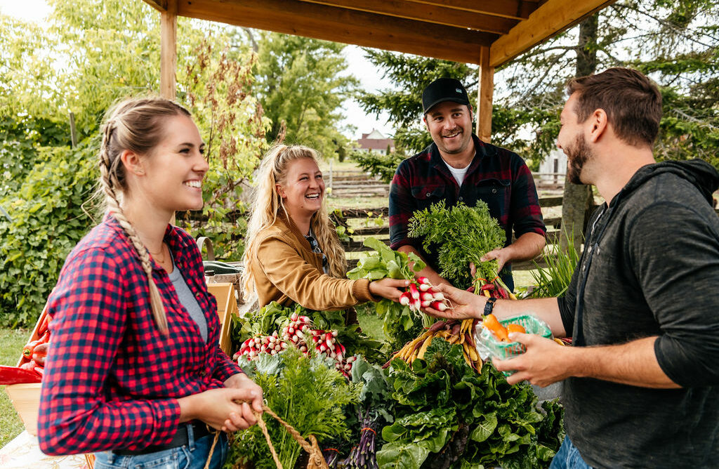 Image of four people at a farm gate stand with lots of locally grown produce