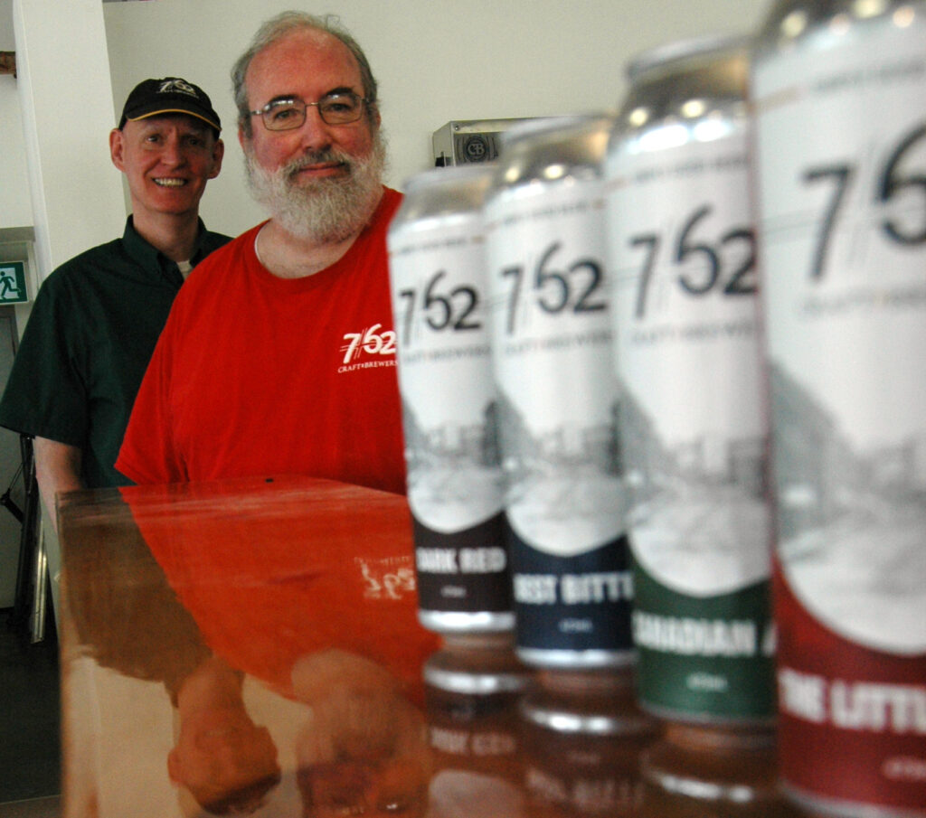 A line of beer cans with two men standing behind them looking at the camera. 7/62 Brewery