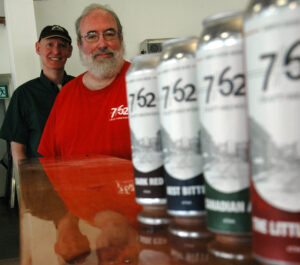Al Shaw and Scott Williams stand together at their business 7/62 Craft Brewers with four cans of beer on display.