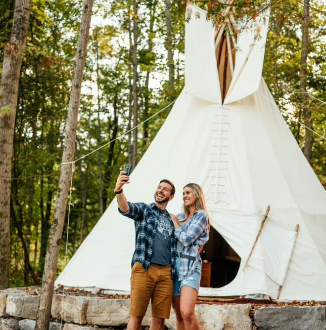 Photo of couple standing in front of a large yurt posing for a selfie photo