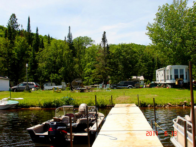 Image of boats next to a dock on water, Baptiste Lake, adjacent the shore, Musky Bay Resort
