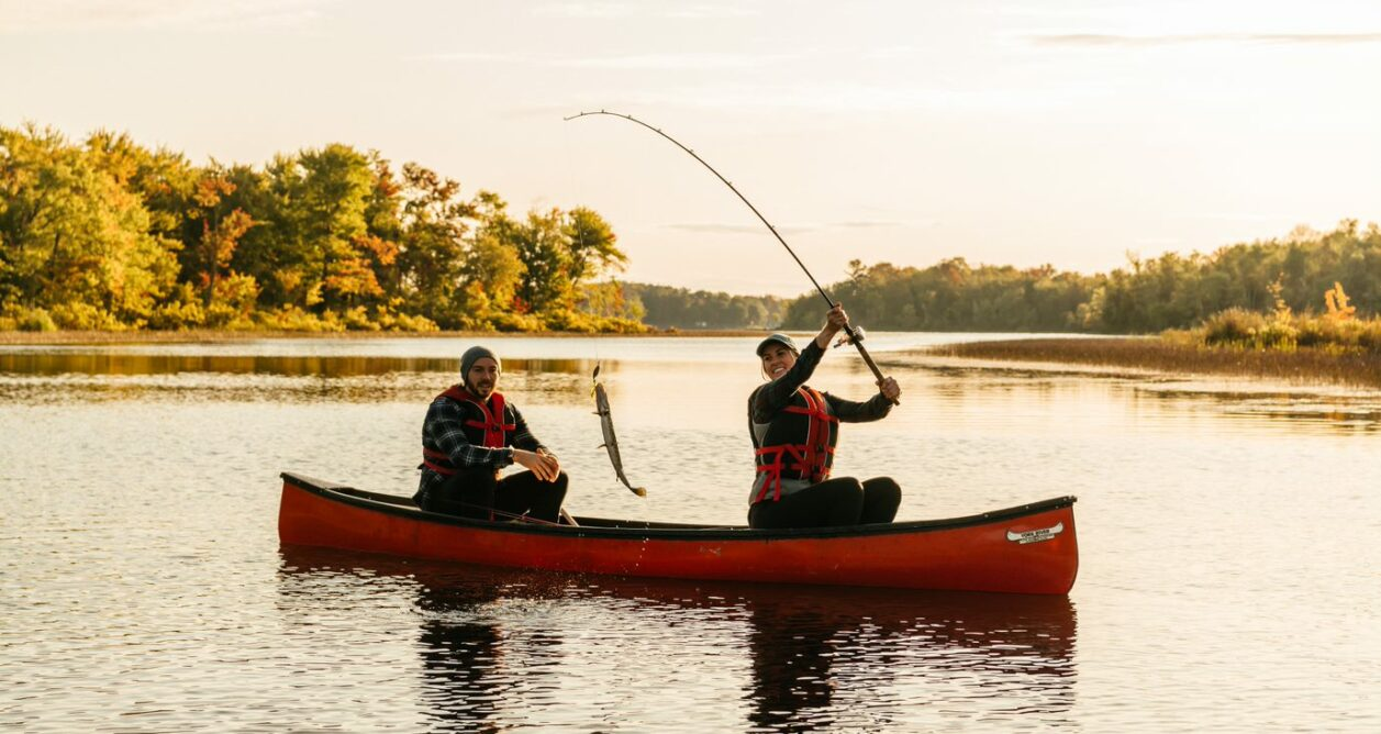 Woman and man in a canoe on a river catching a fish