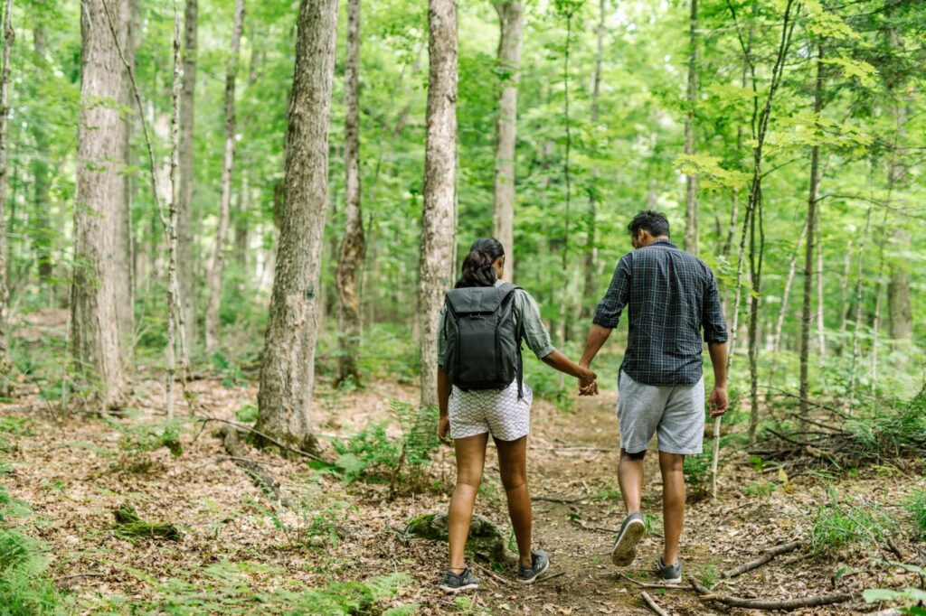 Woman and man holding hands and walking on a trail through the woods