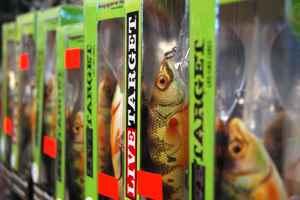 Fishing lures in boxes on display in a store.