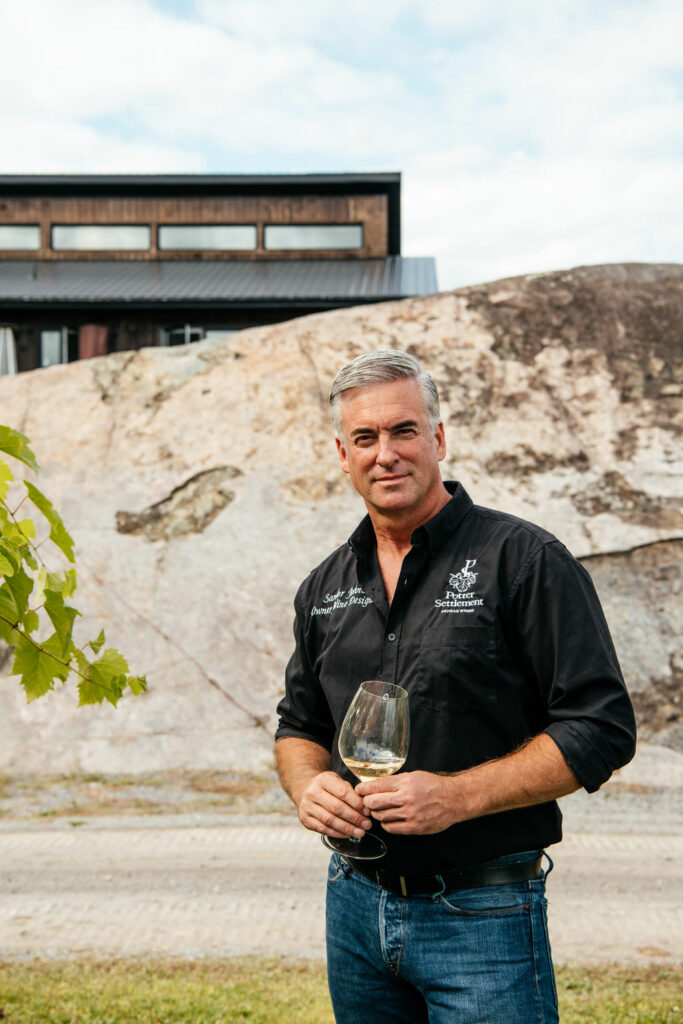 A man, owner, Sandor Johnson holding a glass of wine standing in front of Potter Settlement Winery.