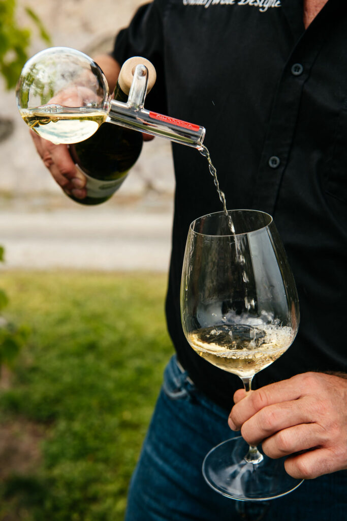 A man pouring a glass of white wine into a glass.