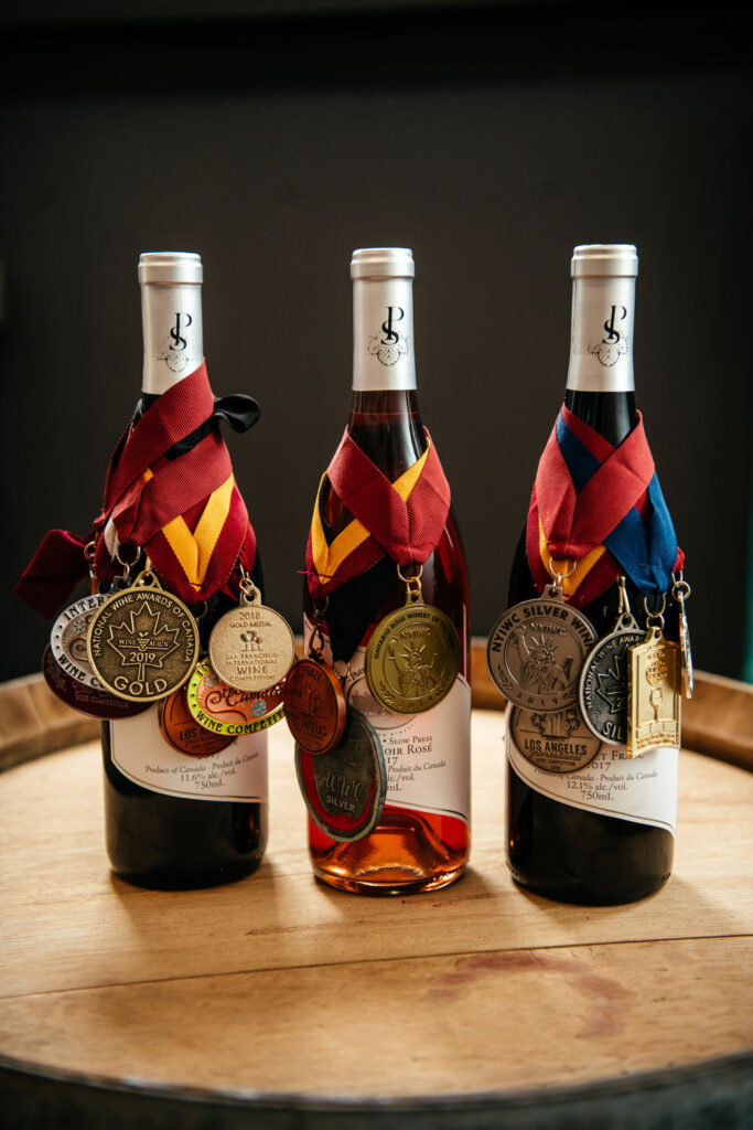 Three bottles of Potter Settlement Winery wines on display with awards.