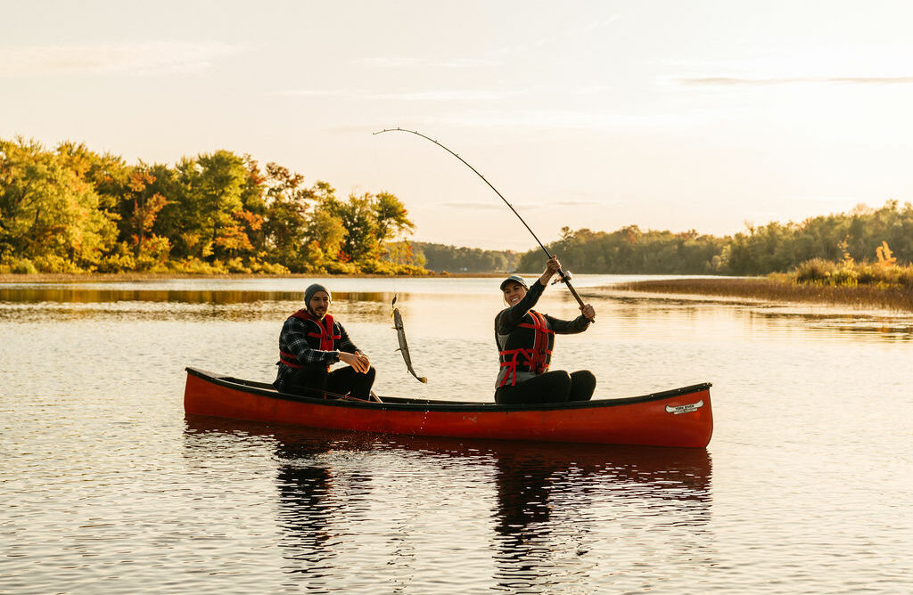A man and woman wearing life jackets are fishing in a canoe on Moira River in Madoc, Ontario; the woman has caught a fish with a fishing rod and is holding the fish out of the water.