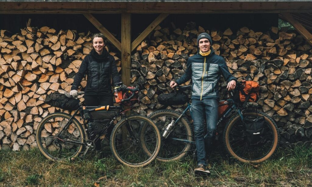 Woman, Laura Voskamp (left), stands with her bicycle  beside man, Adam Tilley (right), who stands with his own bicycle; both are standing in front of a wood stack.