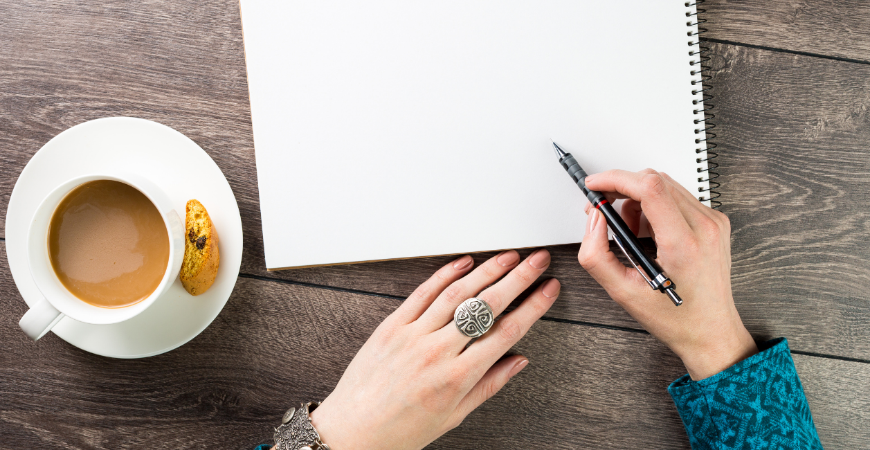 hand holding a pencil resting on a notebook and a cup of coffe beside her